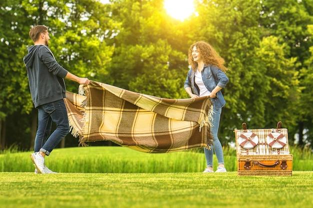 幸せなカップルは緑の公園でカバーを保持します