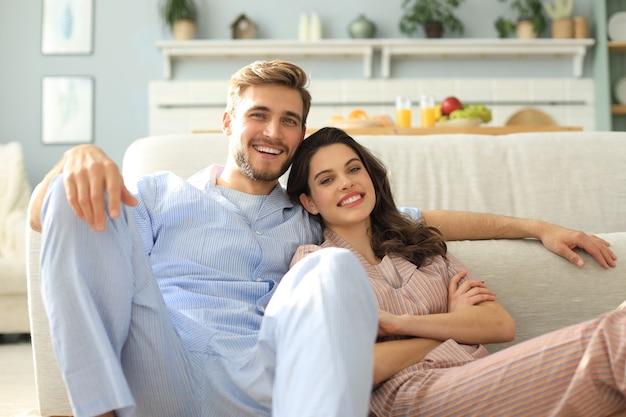 リビングルームのソファの床の背景に座っているパジャマで幸せなカップル。