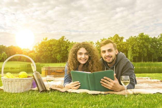 幸せなカップルは公園で横になって本を読みました