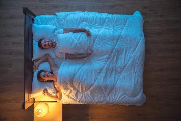 Счастливая пара лежит на кровати. вечер ночное время. вид сверху