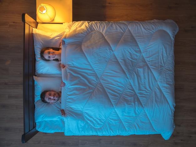 Счастливая пара спит на кровати. вечер ночное время. вид сверху