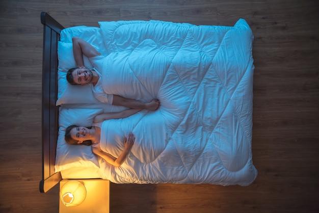 Счастливая пара спит на кровати. ночное время. вид сверху