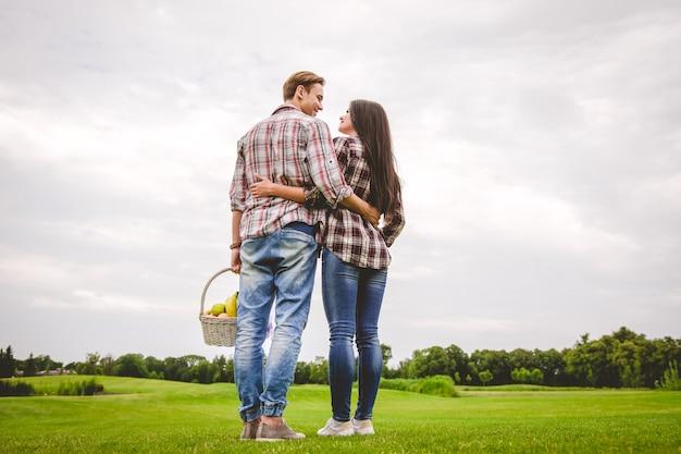 幸せなカップルは草の上に立つ