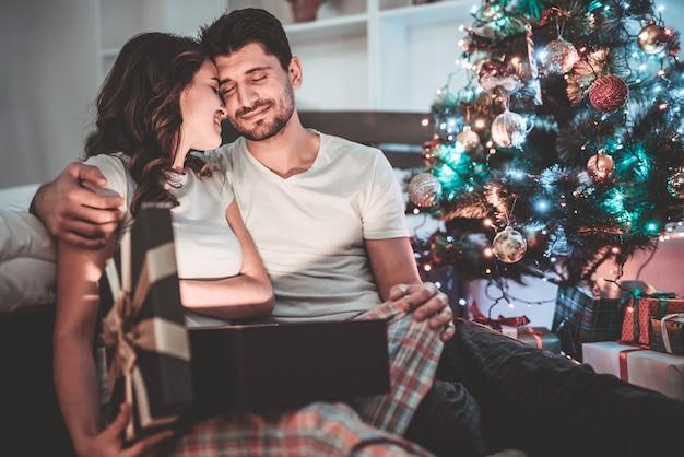 Счастливая пара распаковывает подарочную коробку возле елки. вечер ночное время