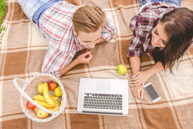 ノートパソコンと果物を持った幸せなカップルが地面に横たわっていた