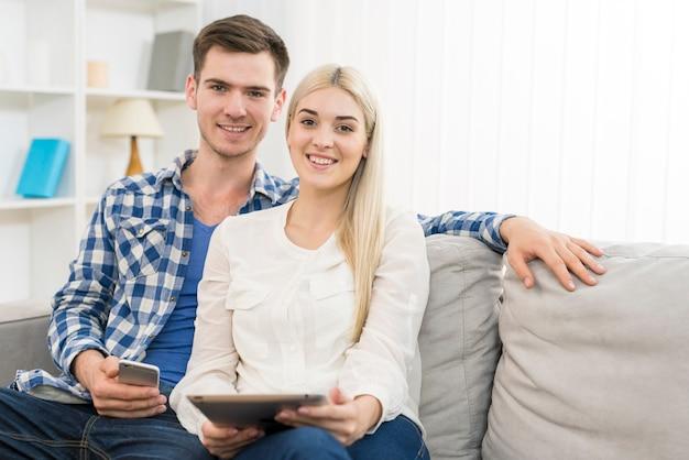 전화와 태블릿을 가진 행복한 커플은 소파에 앉아 있다
