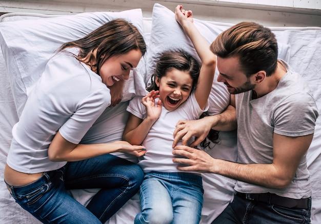 ベッドで喜んで幸せな娘と両親