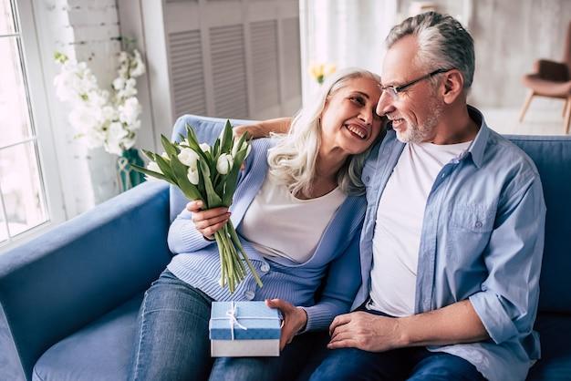 Счастливый пожилой мужчина делает подарок женщине с цветами