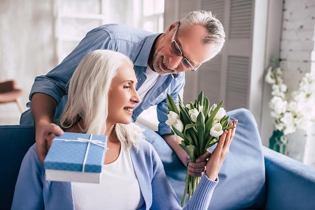 Счастливый пожилой мужчина дарит цветы и подарок женщине