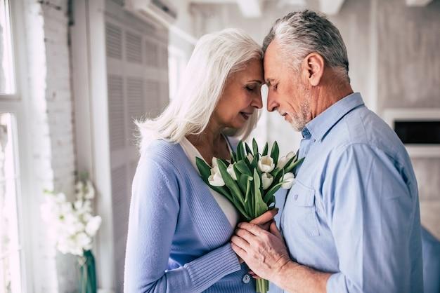 Счастливая пожилая женщина и мужчина, стоящий с цветами