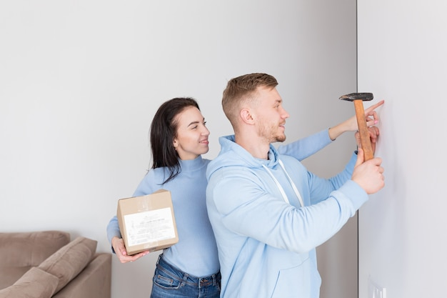 幸せな家族は新しいアパートに引っ越しました、男は壁に絵を掛けます