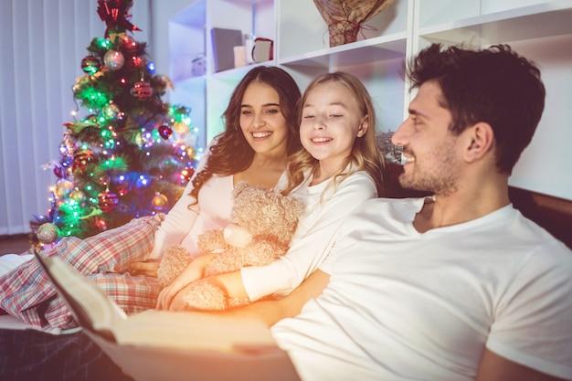 Счастливая семья читала сказку в постели возле елки. вечернее время