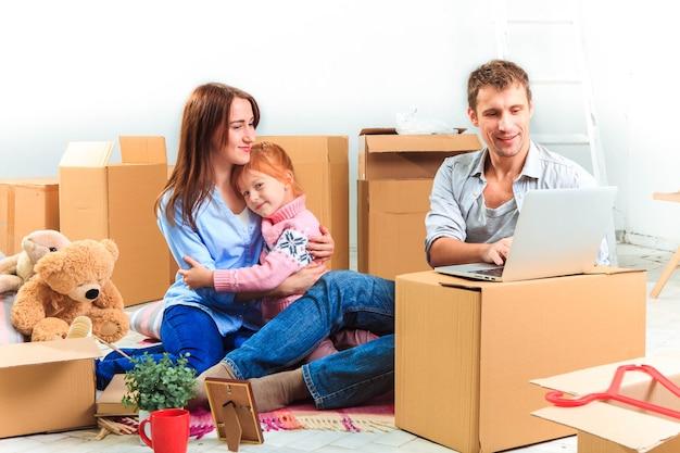 상자 배경에서 수리 및 재배치 시 노트북을 사용하는 행복한 가족