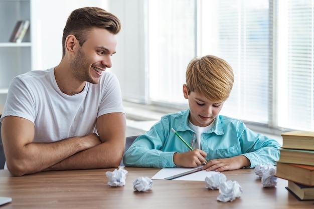 행복한 아버지와 아들이 책상에 앉아 종이에 그림을 그리고 있다