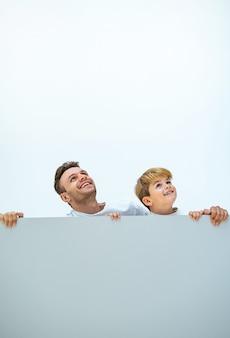 행복한 아버지와 아들이 벽 뒤에 서 있다