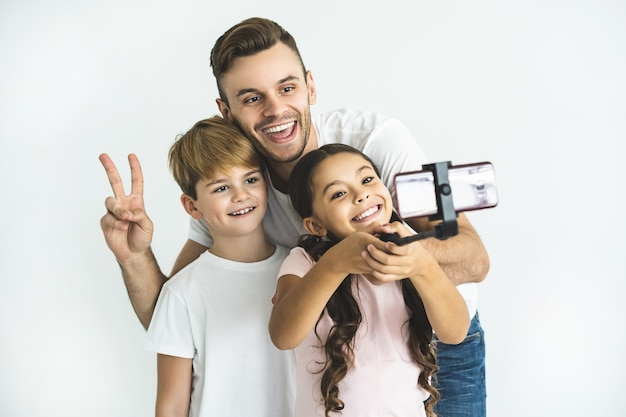 幸せな父と子供たちは白い背景でselfieを取る