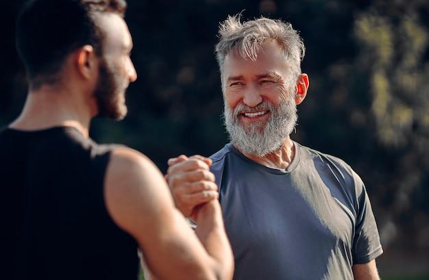 야외에서 인사하는 행복한 아버지와 아들
