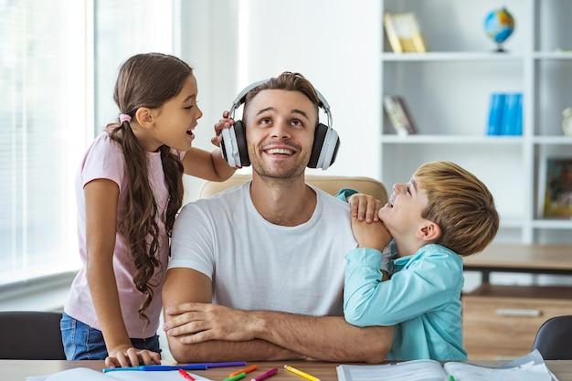 デスクで子供たちと遊ぶヘッドフォンで幸せな父