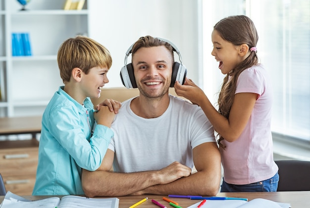 デスクで男の子と女の子と一緒に座っているヘッドフォンで幸せな父