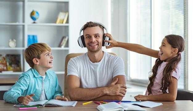 デスクで子供たちと一緒に座っているヘッドフォンで幸せな父