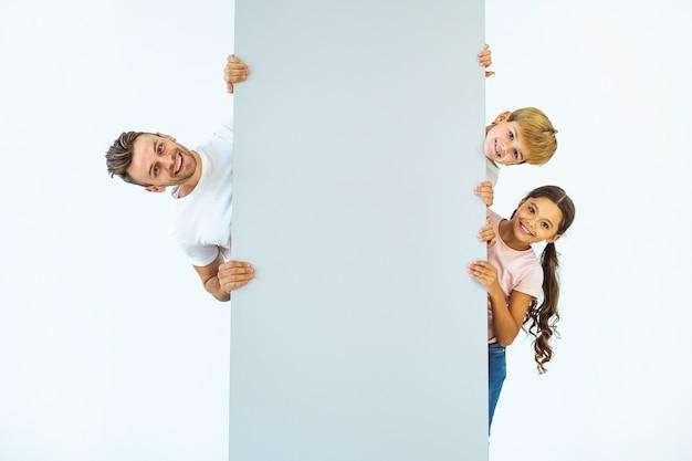 소년과 소녀가 있는 행복한 아버지는 벽 뒤에 서 있다