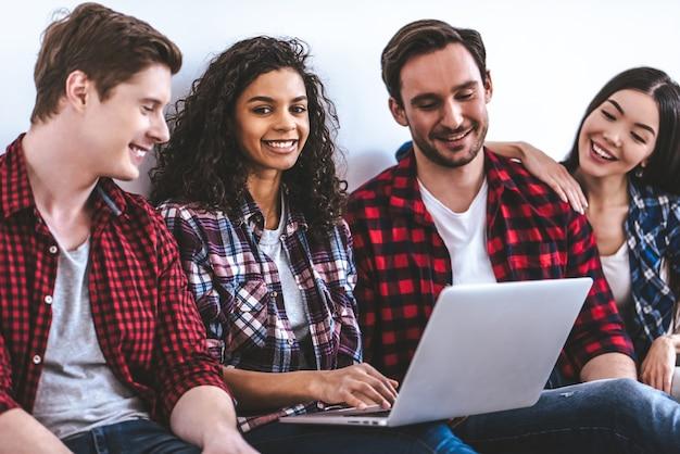 Счастливые четыре человека с ноутбуком сидят на полу