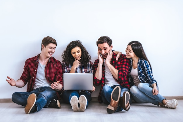 Счастливые четыре человека с ноутбуком, сидя на белом фоне