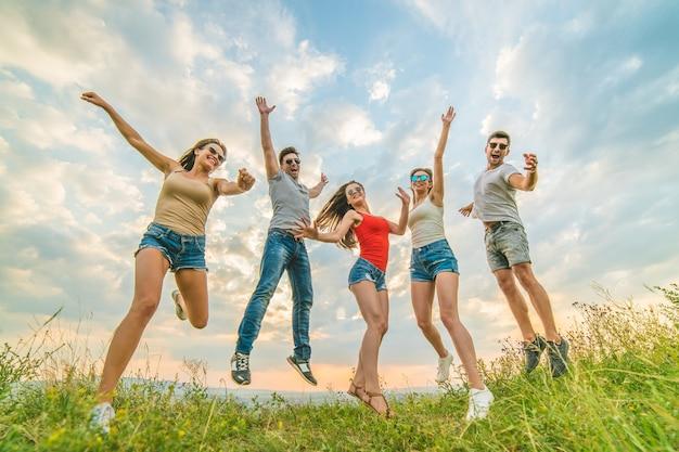 Счастливые друзья прыгают на фоне облаков