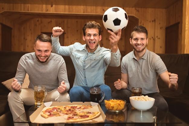 Счастливые друзья смотрят футбол возле стола с едой