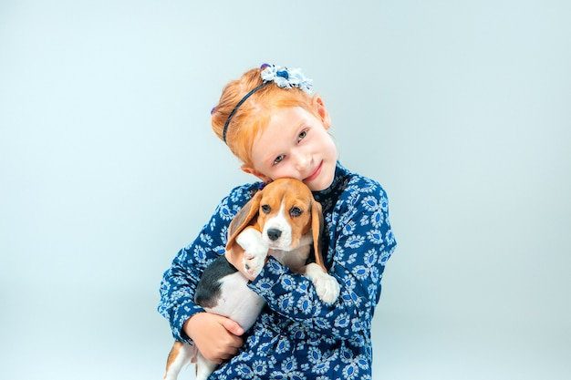 Счастливая девушка и щенок бигля на серой стене