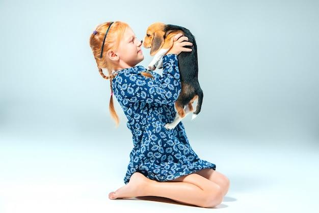 행복 한 소녀와 회색 벽에 비글 강아지