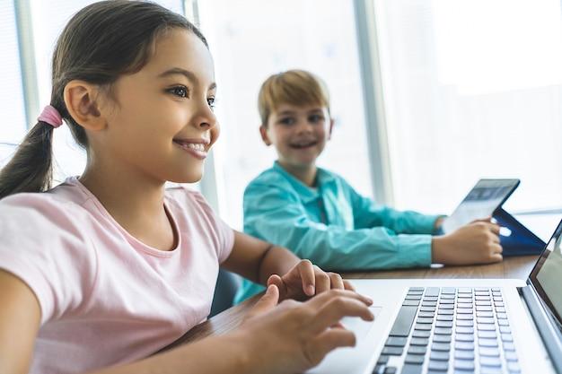 Счастливая девушка и мальчик сидят за столом с ноутбуком и планшетом