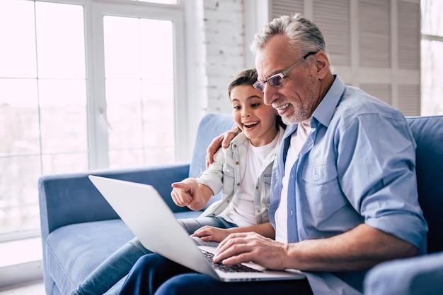 소파에서 노트북을 사용하는 행복한 소녀와 할아버지