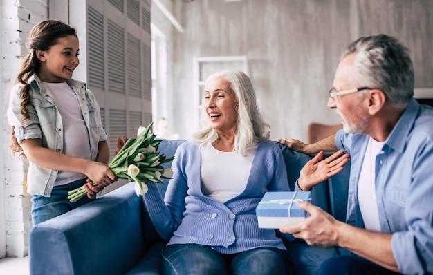 Счастливая девочка и дедушка дарит цветы и подарок бабушке