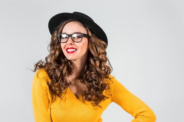 Счастливая девушка в очках и шляпе на серой стене