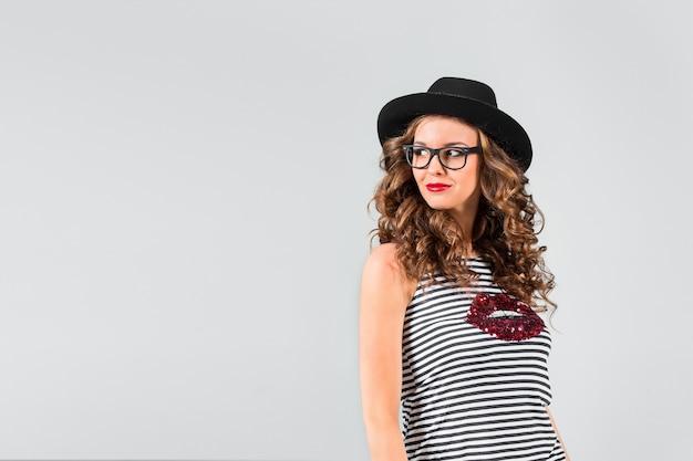 Счастливая девушка в очках и шляпе на сером