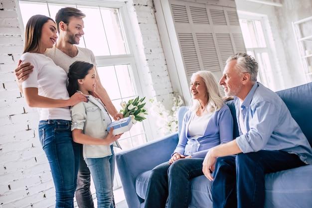Счастливая девушка с родителями делает подарок бабушке и дедушке с цветами