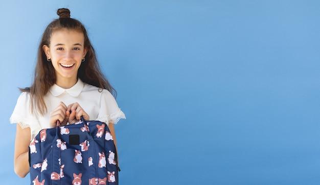 ランドセルを持つ幸せな女の子は、コピースペースと青い背景に笑っています