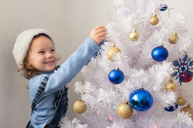 행복한 어린 소녀는 크리스마스 트리를 드레스