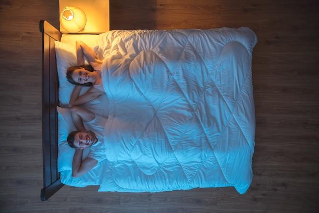 Счастливые влюбленные лежали на кровати. вечер ночное время. вид сверху