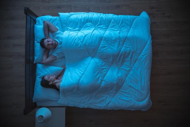 Счастливые любовники спят на кровати. вечер ночное время. вид сверху