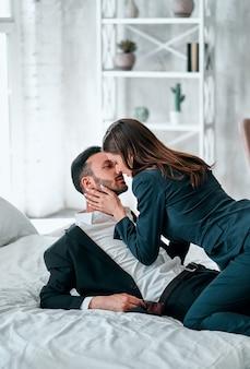 ベッドでキスするスーツを着た幸せな男と女