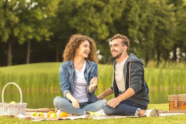 幸せな男と女は公園でイヤホンを持って座っています