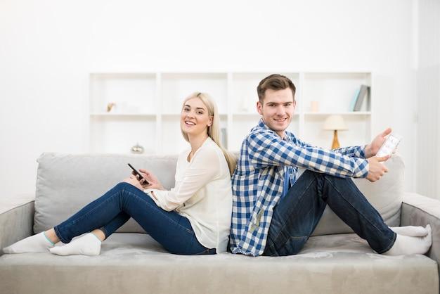 전화와 태블릿을 가진 행복한 남녀가 소파에 앉아 있다