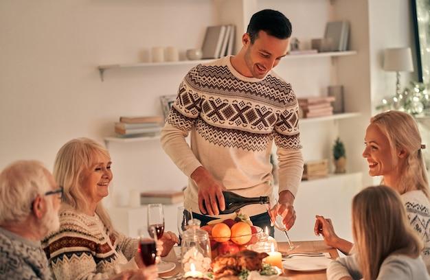 Счастливый человек наполняет фужеры над праздничным столом