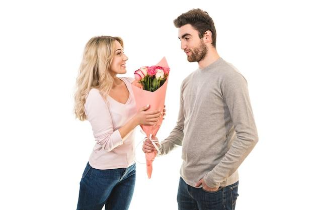 Счастливый человек дарит цветы подруге на белом фоне