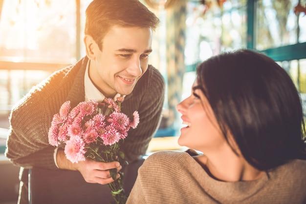 Счастливый мужчина дарит цветы женщине в ресторане