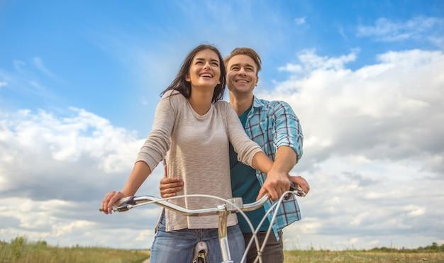 Счастливый мужчина обнимает женщину на велосипеде