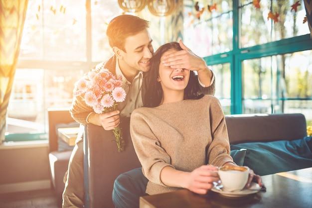 Счастливый мужчина делает сюрприз из цветов для подруги в ресторане