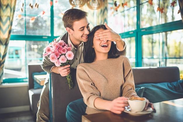 Счастливый мужчина делает сюрприз из цветов для женщины в ресторане